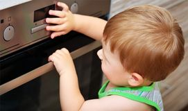 Child playing with electric oven. Dangerous situation in the kitchen. Child playing with electric oven Stock Photography