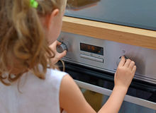 Child playing with electric oven. Dangerous situation in the kitchen. Child playing with electric oven Royalty Free Stock Photo