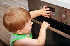 Child playing with electric oven. Dangerous situation in the kitchen. Child playing with electric oven stock image