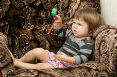 Child playing emotional imagining something. On armchair at home Stock Photo
