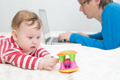 Child playing while father is working on laptop Royalty Free Stock Photography