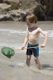 Child playing with a fishing net. Royalty Free Stock Photography