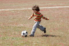 Child playing football Stock Images