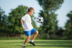 Child playing football Stock Image
