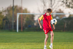 Child playing football. On a soccer field Stock Photo