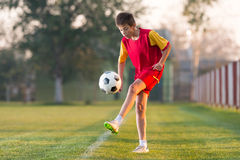Child playing football. On a soccer field Royalty Free Stock Photo