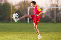 Child playing football. On a soccer field Royalty Free Stock Photography