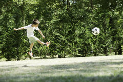 Child playing football in a stadium Royalty Free Stock Photography