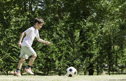 Child playing football in a stadium Stock Photo