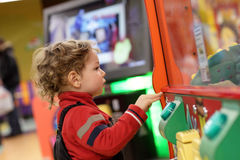 Child playing on game machine stock images