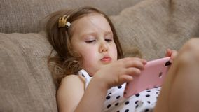 Child playing a game on a mobile phone. Baby girl downloads the application on the smartphone.  stock footage