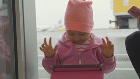 Child playing game on tablet and rejoices in the victory with funny emotions. Little cute girl playing game on tablet and rejoices in the victory with funny stock video footage