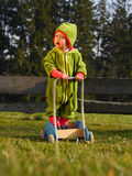 Child playing in the garden with a barrow. Girl stands in a barrow Stock Image