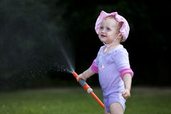 Child playing with garden hose. Cute young girl playing with sprinkling hose in garden; green background royalty free stock image