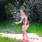 Child playing with garden water slide Stock Photography