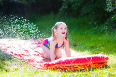 Child playing with garden water slide Royalty Free Stock Images