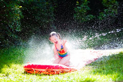 Child playing with garden water slide Stock Image