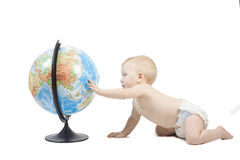 Child playing with globe. Little baby play with terrestrial globe and learn it, his hand is on pacific ocean . Isolated on white Stock Images