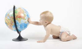 Child playing with globe. Little baby play with terrestrial globe and learn it, his hand is on pacific ocean Stock Photography
