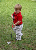 Child playing golf. Cute young boy playing with golf club Royalty Free Stock Photos