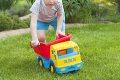 A child is playing on the grass with a big red toy car Royalty Free Stock Photos