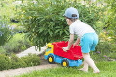 A child is playing on the grass with a big red toy car. A child is playing in the summer on the grass with a big red toy car, playing outdoors Royalty Free Stock Images