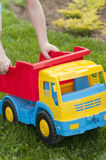 A child is playing on the grass with a big red toy car. A child is playing in the summer on the grass with a big red toy car, playing outdoors Royalty Free Stock Photos