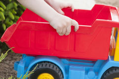 A child is playing on the grass with a big red toy car. A child is playing in the summer on the grass with a big red toy car, playing outdoors Royalty Free Stock Photography