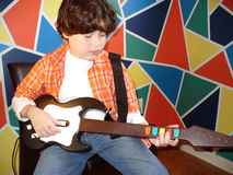 Child playing guitar. In own room stock photos