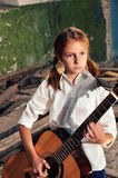 Child playing guitar in grunge ruined room Stock Photos
