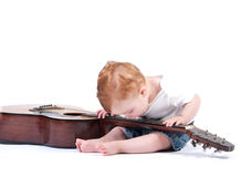 A child playing a guitar with his teeth Royalty Free Stock Photos