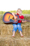 Child playing guitar instrument. A happy and smiling preschool age farm girl playing the guitar while sitting on straw bales and dressed in a red shirt and blue Stock Photo