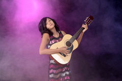Child playing guitar on stage Stock Photography