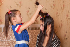 Child playing hairdresser with mother. Royalty Free Stock Photos