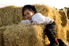 Child playing in a haystack. Royalty Free Stock Photo