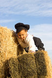 Child playing in a haystack. Royalty Free Stock Image