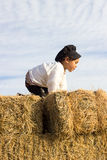 Child playing in a haystack. Stock Photo