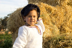 Child playing in a haystack. Royalty Free Stock Photography