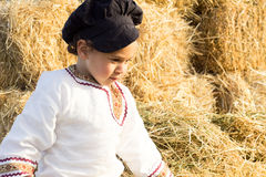 Child playing in a haystack. Royalty Free Stock Images