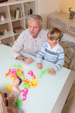 Child playing with his grandfather royalty free stock photos