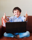 Child playing with his laptop with thumbs up Royalty Free Stock Images