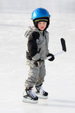 Child playing hockey. Boy stands with hockey stick on outdoor rink Stock Photo