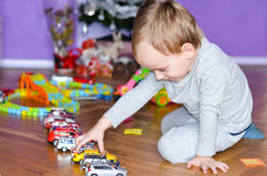 Child playing  at home. Cute blond  Child playing at home with colorful cars Stock Photos