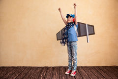 Child playing at home. Happy child playing at home. Kid having fun with toy paper wings Royalty Free Stock Photo