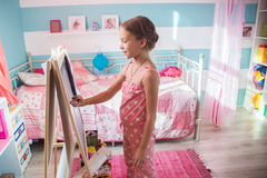Child playing at home. 7-8 years old child drawing on easel in child room at home Royalty Free Stock Image