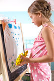 Child playing at home. 7-8 years old child drawing on easel in child room at home Royalty Free Stock Photo