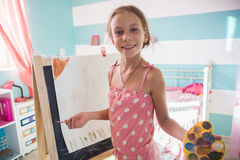 Child playing at home. 7-8 years old child drawing on easel in child room at home Stock Images