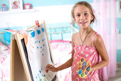 Child playing at home. 7-8 years old child drawing on easel in child room at home Royalty Free Stock Photography