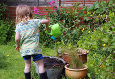 Child playing with watering can. Stock Photo