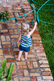 Child playing with a Hose stock photography